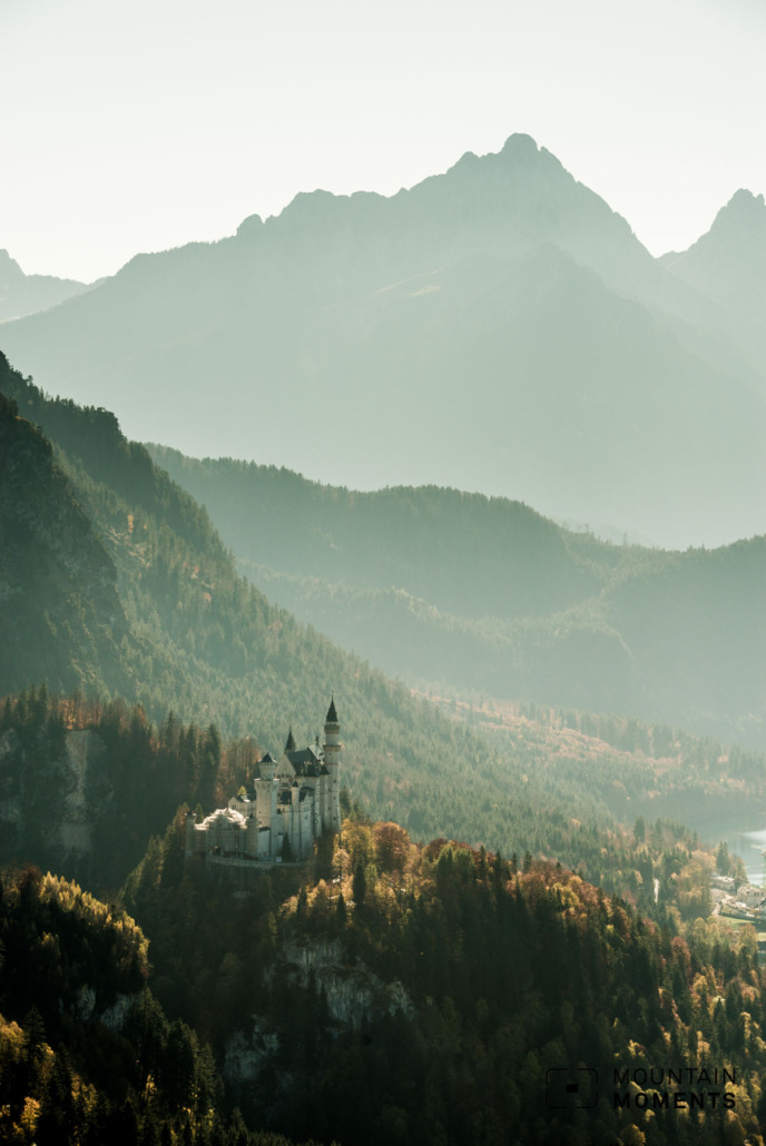 One of the most romantic places in Germany: Neuschwanstein Castle in the autumn light in front of an alpine mountain landscape.